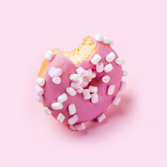 Fototapete - Bitten icing donut with marshmallows on pink background. Monochrome pastel colors