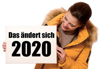 Fröhliche junge Frau hält Schild: Das ändert sich 2020