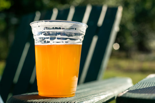 Beer in a clear plastic cup, on the armrest of a patio chair
