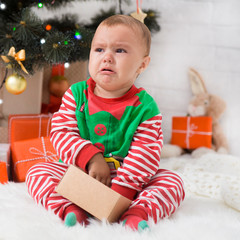 Little baby elf with present box crying near Xmas tree