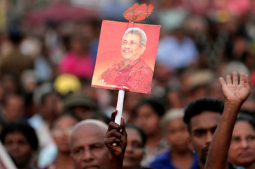 A supporter of Sri Lanka People's Front party presidential election candidate and former wartime defence chief Gotabaya Rajapaksa holds a picture of him during the final election campaign rally in Homagama