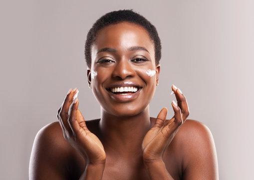 Portrait Of Joyful African Girl Applying Moisturizing Lotion on Face