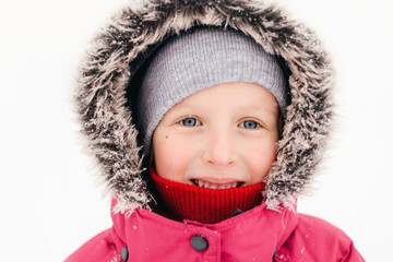 Closeup portrait of cute adorable Caucasian smiling girl child in pink jacket fur hood during cold winter snowy chilling freezing day at snowfall. Kids outdoor seasonal activity. Funny face.