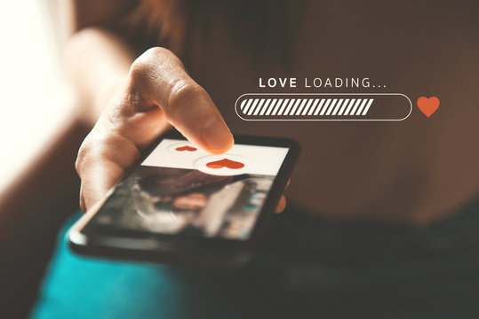 Love loading progress, Finger of woman pushing heart icon on screen in mobile smartphone application. Online dating app, valentine's day concept.