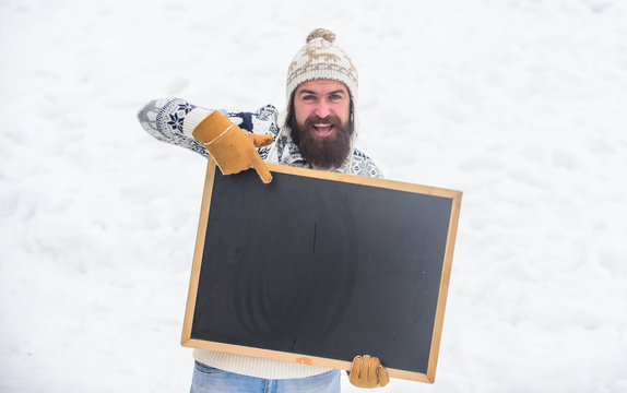 look here. bearded man in warm clothes. Happy new year. happy hipster with blackboard. man advertising board. Copy space. winter season. ski and sledge. Christmas sales. winter holiday. Party here