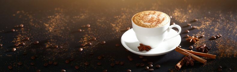 White cup with coffee on a black background, top view. Coffee with cinnamon. Long banner with copy space. Macro photo.