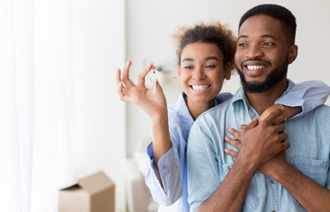African American Couple Holding Key Embracing Standing In New Flat