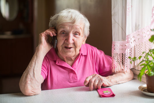 Elderly woman talking on the phone sitting at the table.