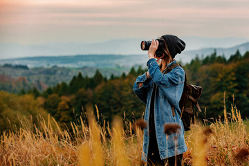 Style girl with camera and backpack at countryside with mountains on background