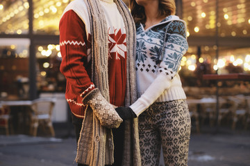 Man and woman are fully prepared for winter time, they are wearing warm festive sweaters and gloves