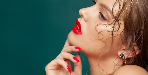 Close-up portrait of beautiful woman with holiday make-up. Perfect red lips and nail design. Gold glitters on her face. Christmas make-up