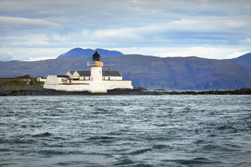 Panoramic view of the cliffs, mountains and valleys of the islands of Inner Hebrides on a cloudy day. Scotland, UK. An old loghthouse close-up