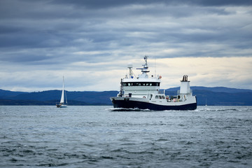 Panoramic view of the cliffs, mountains and valleys of the islands of Inner Hebrides on a cloudy day. Scotland, UK. White sloop  rigged yacht and fishing boat close-up