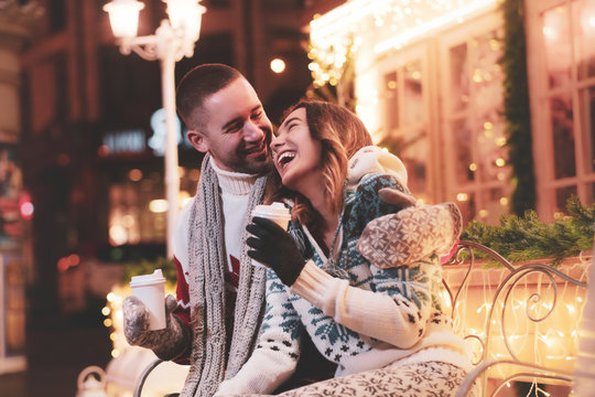 Young happy couple enjoying their romantic date while warming up with hot beverages.