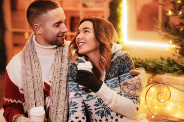 Inbetween Christmas decorations romantic couple enjoying hot drinks while have a date.