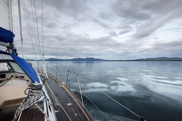 Wooden sloop rigged yacht sailing on a cloudy day, a view from the deck to the bow, mast and sails. Inner Hebrides, Scotland, UK