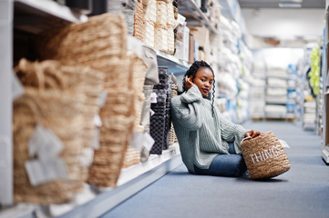 African woman choosing basket with things for her apartment in a modern home furnishings store.