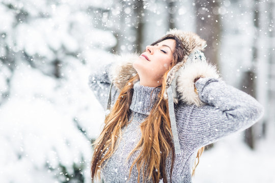 brunette, laughing, young, beautiful, woman with gray knit sweater, dancing in winter forest