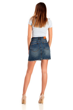 Woman in white t-shirt with blue jeans mini skirt with beige high heel shoes posing isolated on white background