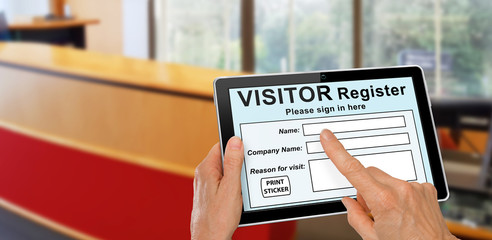 Visitor completing a sign in register form on computer tablet