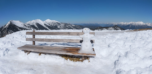 little snowman sitting at a wooden bench in the bavarian alps