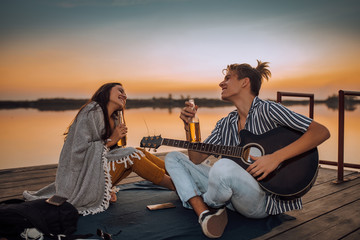 Canvas Prints Bar Young couple drinking beer and enjoying, while guy playing a guitar to his girlfriend by the river