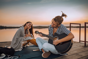 Canvas Prints Bar Attractive guy playing a guitar to his girlfriend by the river