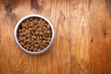 Dog food in bowl on wooden table. From above. Copy sapce Wall mural