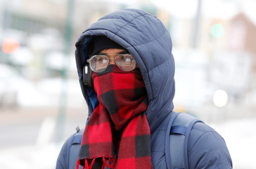 A university student waits in the cold for a campus bus in Detroit, Michigan