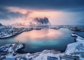 Printed kitchen splashbacks Night blue Aerial view of snowy mountain, village on sea coast, orange sky at sunset in winter. Top view of Reine, Lofoten islands, Norway. Moody landscape with high rocks, houses, rorbu, reflection in water