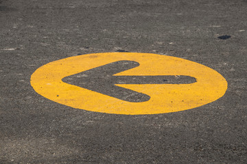 Direction arrow in parking lot - Yellow circle with arrow facing left unpainted in middle on grungy grainy grey blacktop surface