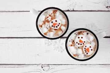 Two cups of holiday hot chocolate with snowman marshmallows. Top view on a white wood background.