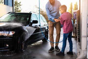 Father and son washing their car at car wash station using high pressure water.
