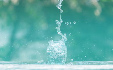 Water splash in glass Select focus blurred background.Drink water pouring in to glass over sunlight and natural green background.Nature conservation concept.
