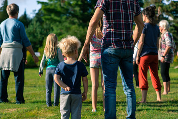 Selective focus and behind view of group of people with young children standing in a grass field on a sunny day