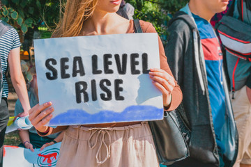 "The phrase "" Sea level rise "" and wave drawn on a paper in woman hands. Caucasian woman with light hair holds a cardboard with an inscription. Global warming. Climate change"
