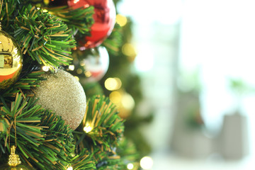 bauble hanging from a decorated Christmas tree. Retro filter effect