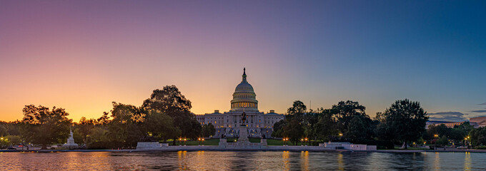 Panoramic image of the Capitol of the United States with the capitol reflecting pool in morning light.