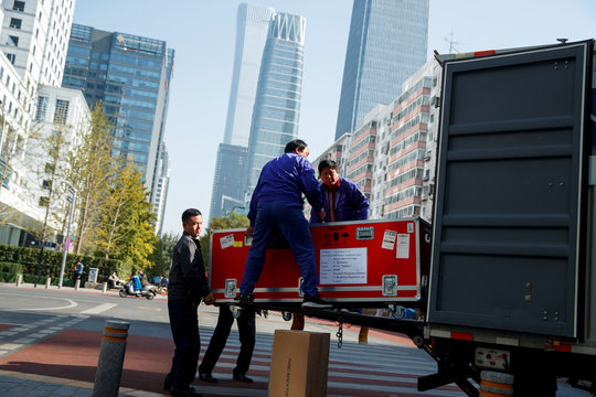 Men unload cargo from the truck of a logistics firm in Central Business District in Beijing