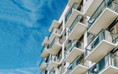 Detail of Modern residential apartment flat building exterior. Fragment of New luxury house and home complex. Part of City Real estate property and condo architecture. Copy space. Blue sky Fotomurales