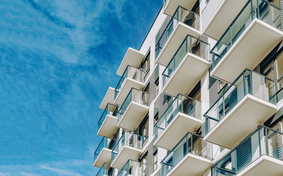 Detail of Modern residential apartment flat building exterior. Fragment of New luxury house and home complex. Part of City Real estate property and condo architecture. Copy space. Blue sky