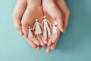 Adult and children hands holding paper family cutout, family home, foster care, homeless charity...