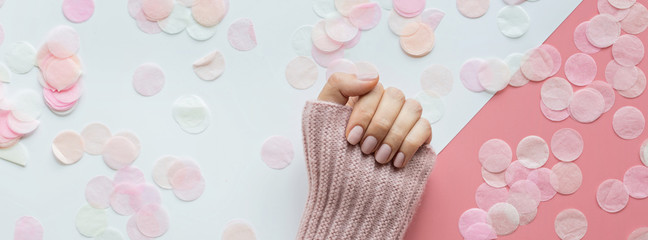 Stylish trendy female pink manicure. Beautiful young woman hands on pink and white background with flowers and place for text. Minimal creative concept. Flat lay, top view, mock up copy space template Wall mural
