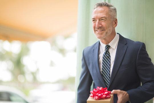 Mature handsome businessman holding a present.