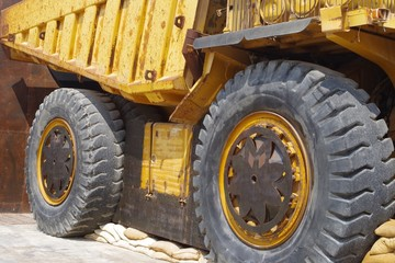 Close up picture of a big yellow mining truck.