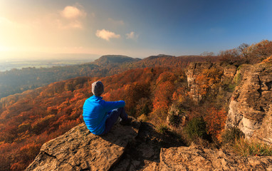 Wanderer sitzt am Hohenstein und genießt den Ausblick über den herbstlichen Süntel