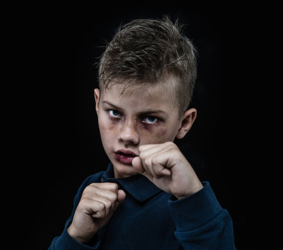 Beaten young boy is ready to fight. Isolated on dark background