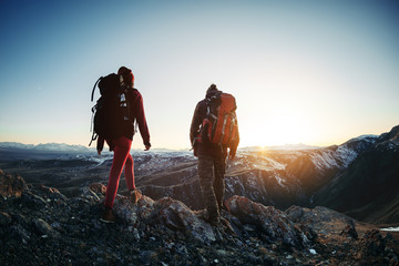 Two hikers walk sunset mountains