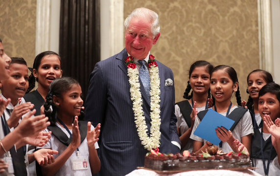 Britain's Prince Charles looks on as children from a school sing a birthday song for him in Mumbai