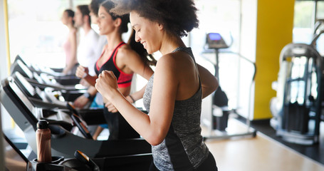 Deurstickers Fitness Group of people exercising in a gym cardio training and running